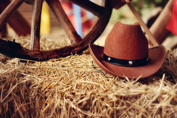 on a haystack the brown cowboy's hat and a wooden wheel lies Wall mural