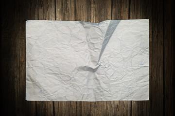 Old damaged paper sheet on a wooden background