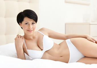 Woman in white perfect bra is lying in the soft bed