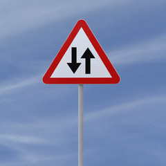 Two way road sign on a blue sky background