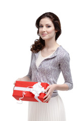 Young woman keeps a gift wrapped in red paper, isolated on white
