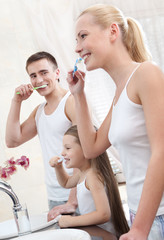 Happy family of three people brush their teeth in bathroom