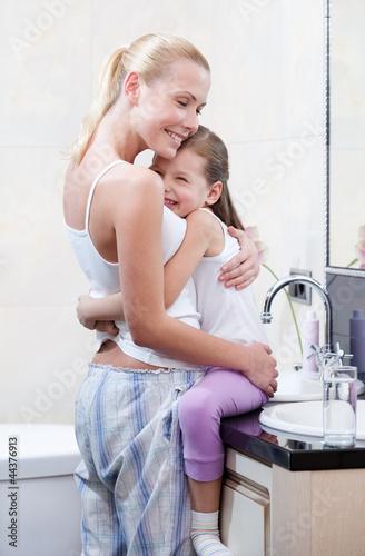 отец смотрит как маленькая дочь моется в ванной