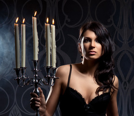 Fashion shoot of a young brunette woman holding candels