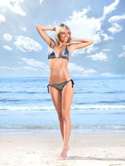 Spoed Foto op Canvas womenART A blond posing in a swimsuit on a sky and water background