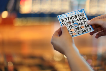 Woman hands hold bingo card with holes