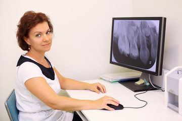 Dentist sits at table with big jaw x-ray image on monitor