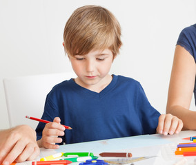 Young boy drawing with colorful pencils
