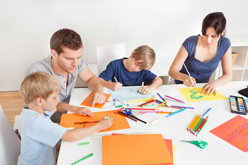 Young family drawing with colorful pencils