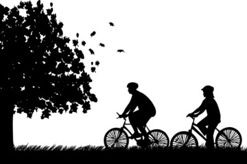 Couple bike ride in park in autumn or fall silhouette