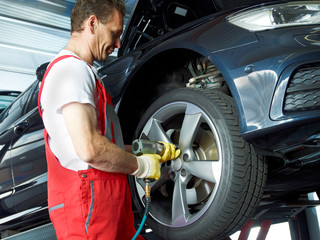 Motor mechanic changes a tyre with new alu rim on a service lift