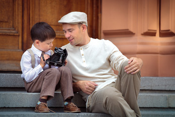 Father and little son with retro camera outdoors