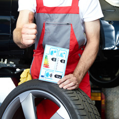 Car mechanic shows thumb up for tire label