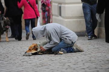 Bettler mit Hund in der Stadt