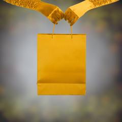 Elegant lady in golden gloves holding shopping bag