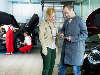 Car mechanic and customer looking at a quotation