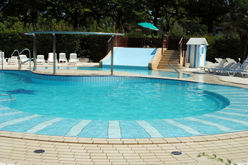 limpid swimming pool and white sunbeds without people