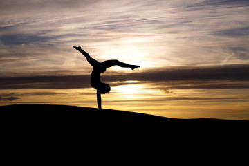 Wall Mural - silhouette of gymnast in sunset