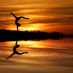 Fototapeta silhouette of female gymnast doing a handstand in sunset obraz