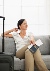 Dreaming young woman with bag holding passport and air ticket