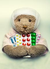 Ill teddy bear in bed