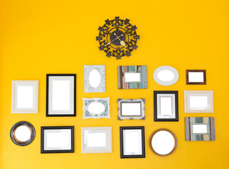Several frames with vintage clock on the yellow wall