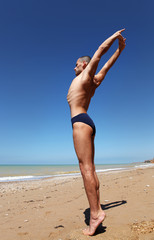 Young man in strong stretching yoga pose