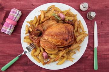 pollo arrosto con patate fritte su tavolo rustico