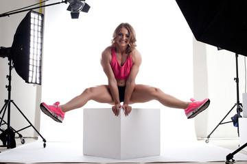 Beauty woman body builder sit on cube in studio