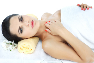 Young beautiful woman relaxing  at spa isolated on white