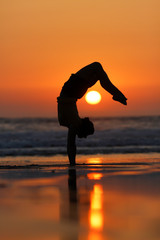 Wall Mural - gymnast in sunset on beach