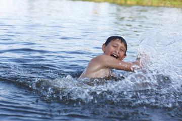 boy in river with splash