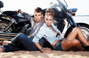 Fototapete - Extreme couple sitting by motorcycle. Adventure and travel
