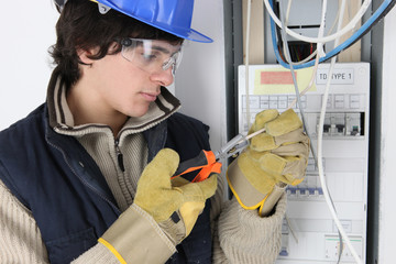 Young electrician working on a fuse box