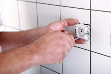 Electrician fitting electrical outlet in bathroom