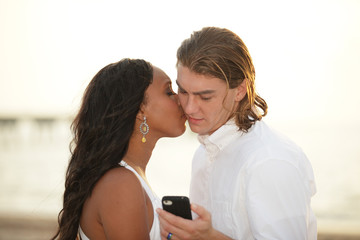 Man secretly texting while being kissed