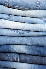 Many jeans stacked in a pile closeup