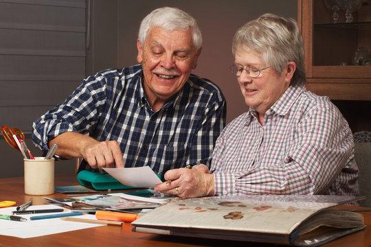 Happy senior couple making a scrapbook