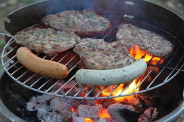 Grillfleisch und verschiedene Bratwürste auf dem Grill