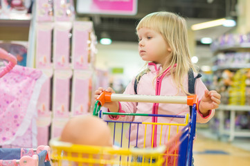 Adorble girl with small shopping cart in kids mall
