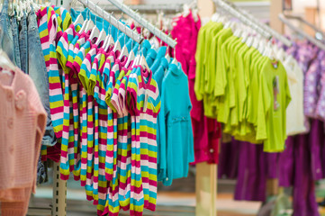 Sweaters and blouses on stands in kids mall