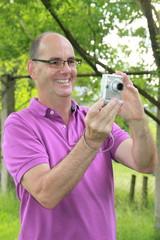 Mann im lila Poloshirt beim Fotografieren im Grünen