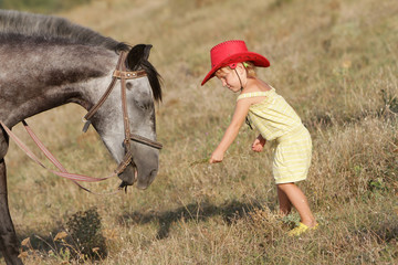 young happy child girl feeding horse on natural background
