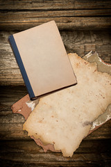 Grungy aged book and papers on wood