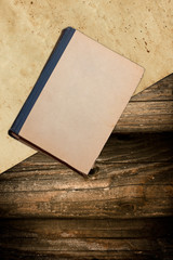 Old book and paper on a faded wooden background