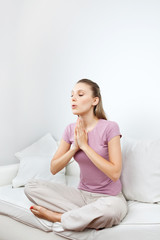 Woman Meditating On Sofa