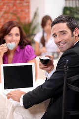 Couple drinking expresso in a cafe with a laptop