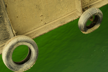 green sea water on the background of tires