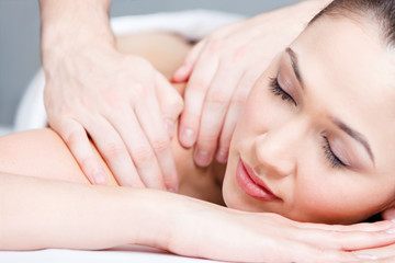 Woman receives body massage at spa salon