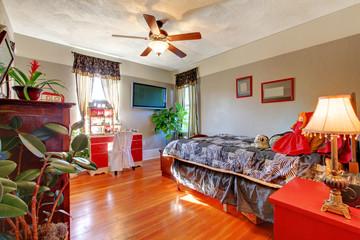 Bedroom with hardwood floor and grey walls.